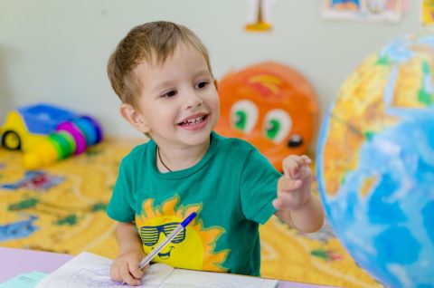 edukacja dzieci z ubogich rodzin, dzieci z ubogich rodzin mają mniejsze szanse na sukces, chłopiec, nauka, globus