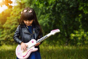 Budować silną samoocenę dziecka, dziewczynka, natura, uśmiech, gitara